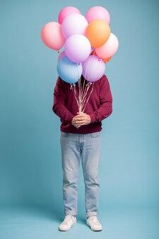 Casual bejaarde man met een heleboel kleurrijke ballonnen verjaardagsverrassing maken voor iemand