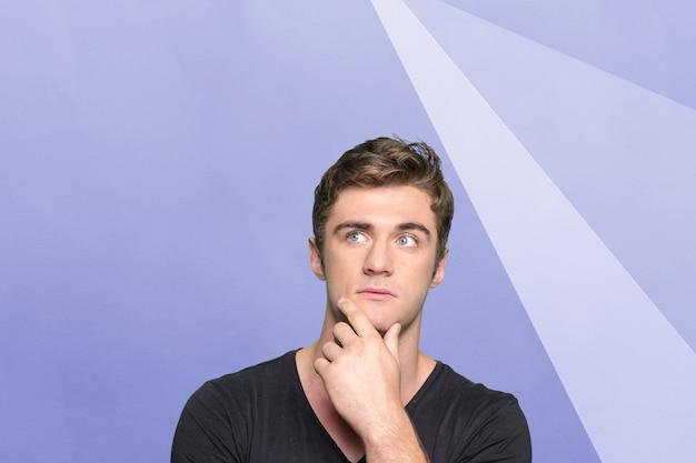 Casual blanke jonge man met doordachte expressie