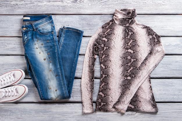 Casual blauwe spijkerbroek en top. top met hoge kraag en schoenen. tweekleurig damessweatshirt tentoongesteld. artikelen uit internetwinkel.