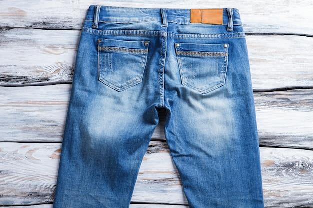 Casual blauwe spijkerbroek met zakken. effen jeans op houten achtergrond. nieuw item in catalogus. denim kledingstuk op winkel showcase.