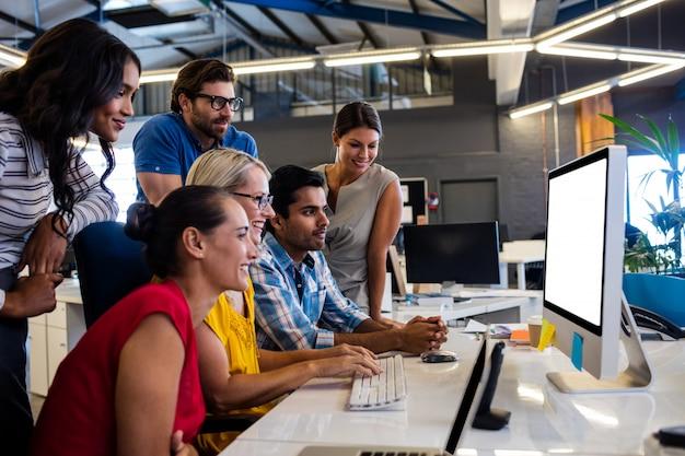 Casual business team dat werkt op één computer