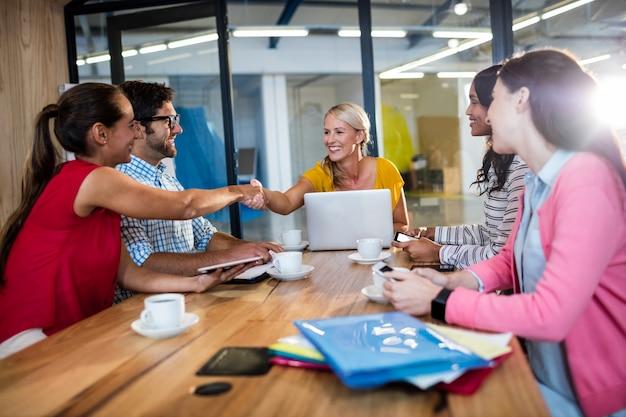 Casual business team handdruk geven