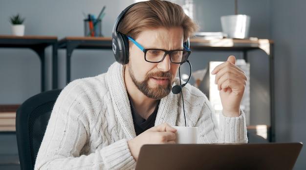 Casual-geklede man met hoofdtelefoon telewerken achter computer, isolatie als gevolg van epidemie