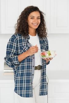 Casual geklede vrouw salade eten