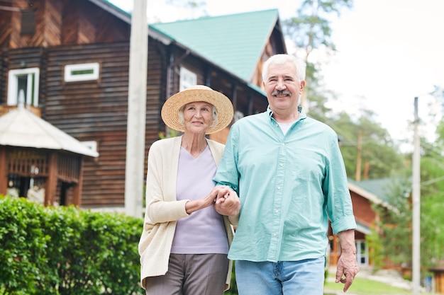 Casual gelukkige senior paar vooruit op het platteland terwijl u geniet van promenade op zomerdag