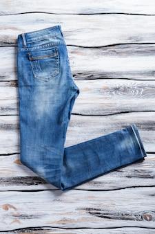 Casual jeans van blauwe kleur meisjesjeans op houten achtergrond eenvoudige broek voor lente stevige stof en ...