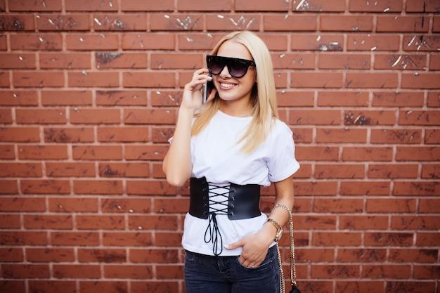 Casual jong blond meisje praten in de telefoon tegen baksteen