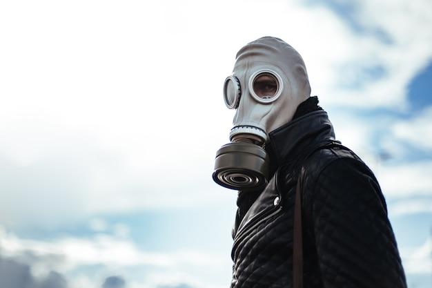 Casual jonge man met een gasmasker op straat in een lege stad. foto met een kopie-spatie