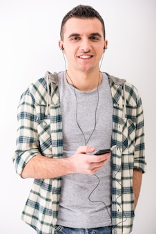 Casual jonge man met mobiele telefoon en hoofdtelefoon.