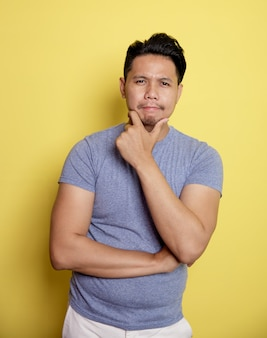 Casual jongeman glimlach denken idee met de kin en een hand op de buik geïsoleerd op een gele kleur achtergrond