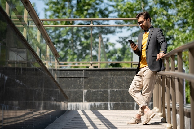 Casual jongeman in beige spijkerbroek, gele trui en donkerblauw jasje scrollen in smartphone door leuningen buitenshuis