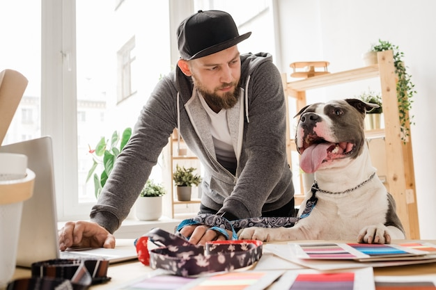 Casual jongeman kijken naar zijn hond terwijl bukken werkplek met laptop en werken aan nieuwe halsband collectie