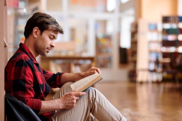 Casual jongeman leesboek zittend door boekenplank in bibliotheek van de universiteit