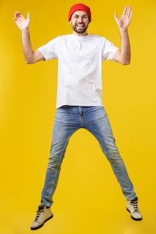 Casual jongeman springen van vreugde op geel goud