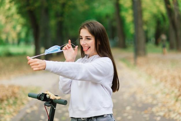 Casual kaukasisch wijfje dat beschermend gezichtsmasker draagt dat stedelijke elektrische autoped berijdt