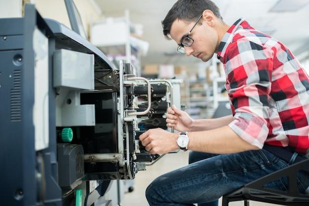 Casual man aan het werk met drukmachine