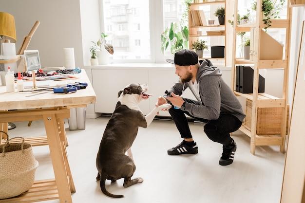 Casual man hurkt terwijl hij thuis met zijn huisdier speelt op de werkplek en hem nieuw speeltje laat zien