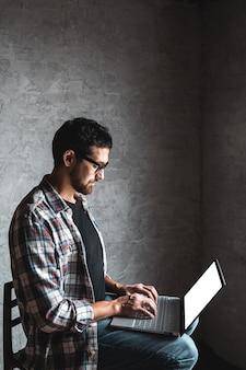 Casual man met laptop over grijze achtergrond. internet, onderwijs, werk, vrije tijd