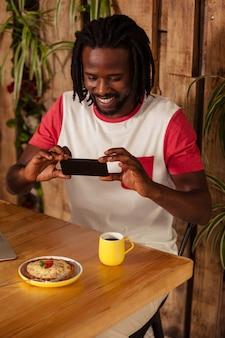 Casual man nemen foto van gebak en kopje koffie