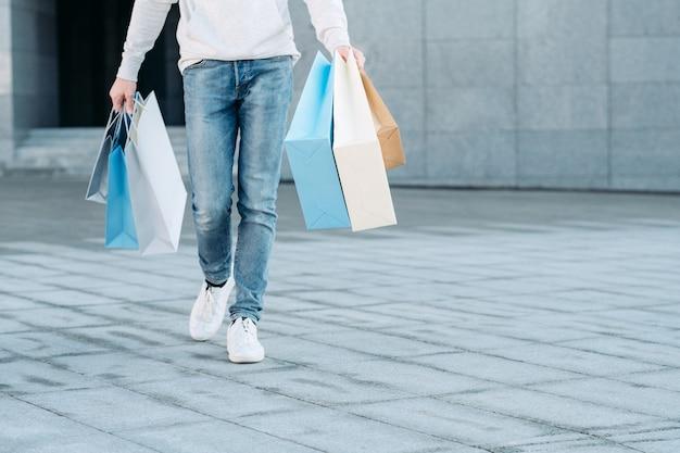 Casual man winkelen vrijetijdsbesteding winkel verkoop benen in spijkerbroek papieren zakken in handen