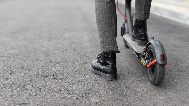 Casual man zijn scooter buiten rijden