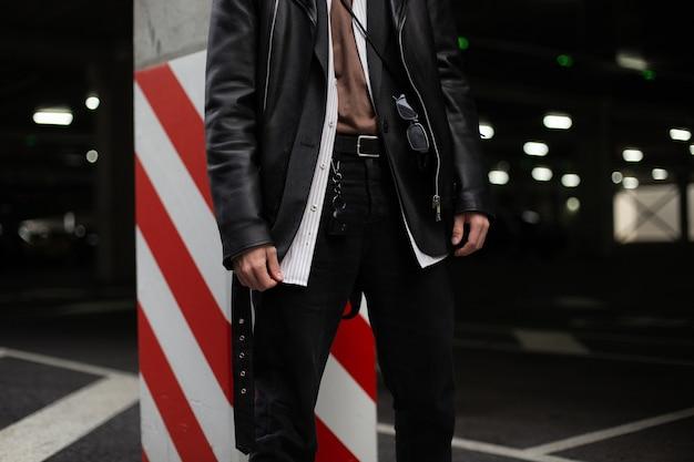 Casual mode oversized kleding en accessoires voor mannen. close up lichaam van een jonge man in een mode-shirt in een zwarte leren jas in retro stijl in vintage jeans in de buurt van een pilaar met rode en witte lijnen.
