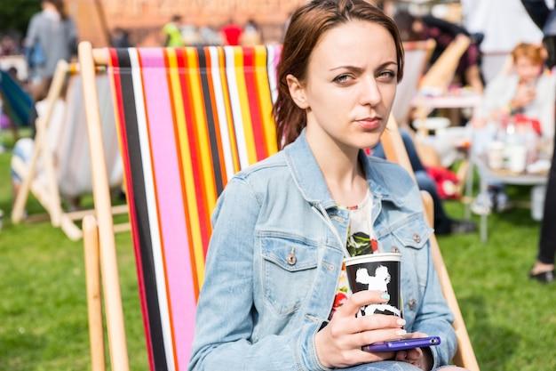 Casual portret van jonge brunette vrouw denim jean jas dragen en mobiele telefoon houden en koffiekopje nemen zittend in gestreepte strandstoel in veld op picknick of outdoor festival