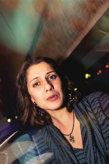 Casual portret van positieve emotionele jonge vrouw in de nachtclub van het restaurant aan tafel. nacht stad levensstijl concept. ruimte kopiëren