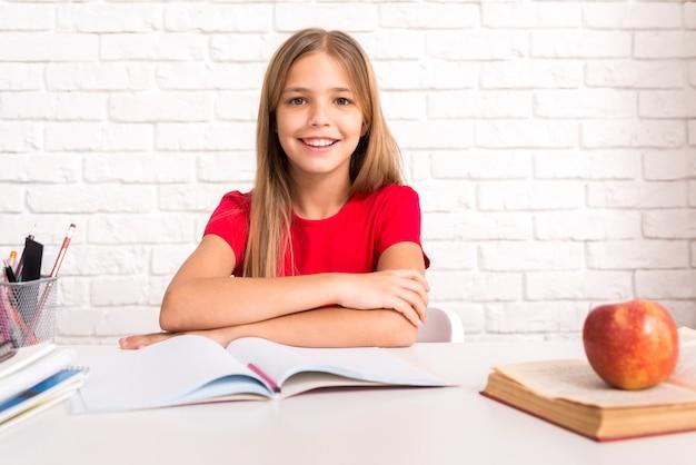 Casual schoolmeisje zittend aan een bureau