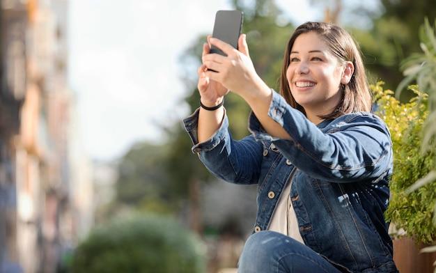 Casual tiener praten een selfie buitenshuis