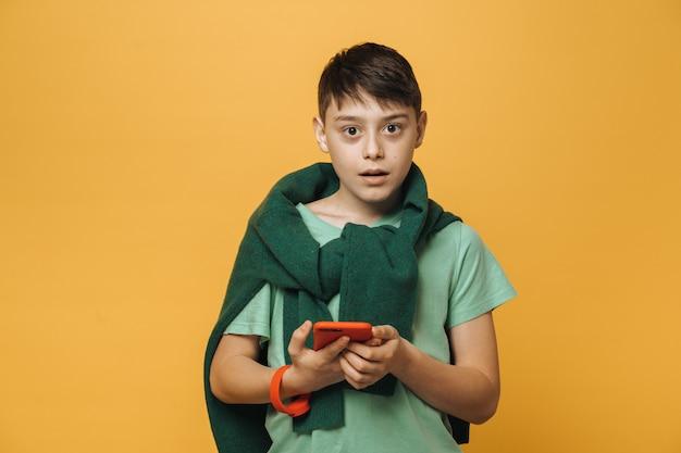 Casual verrast jongen in lichtgroen t-shirt en met zijn trui om zijn schouders gebonden, houdt mobiele telefoon, verrast, over gele muur. levensstijl concept