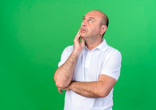Casual volwassen man hand zetten wang geïsoleerd op groen