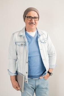 Casual volwassen man in blauwe spijkerbroek en pullover, wit jasje, bril en muts staande over witte muur