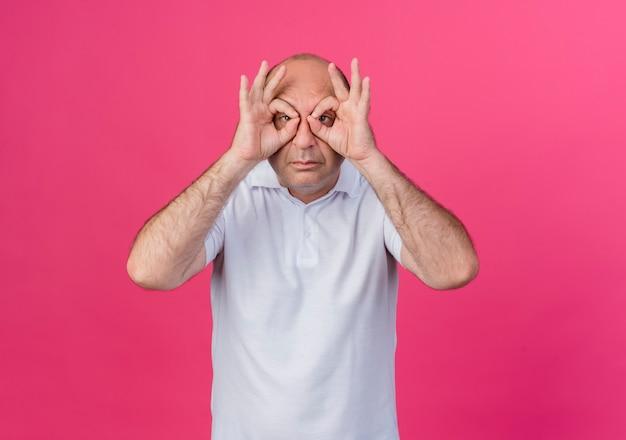 Casual volwassen zakenman doet blik gebaar camera met behulp van handen als verrekijker geïsoleerd op roze achtergrond met kopie ruimte