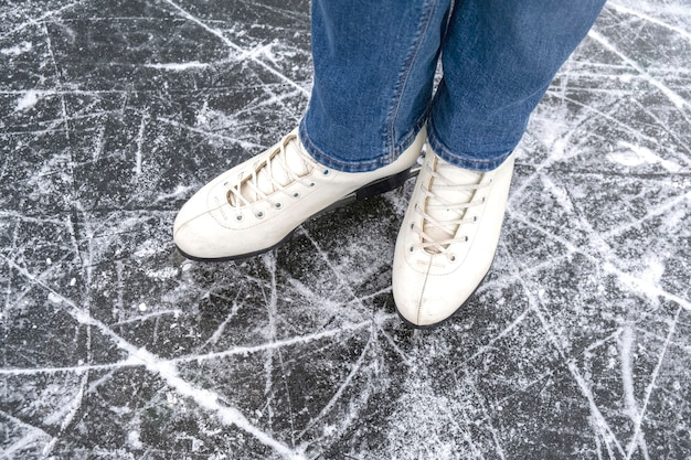 Casual vrouw kijken in schaatsen en jeans op ijs macro bovenaanzicht
