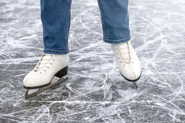 Casual vrouw kijken in schaatsen en jeans op ijs