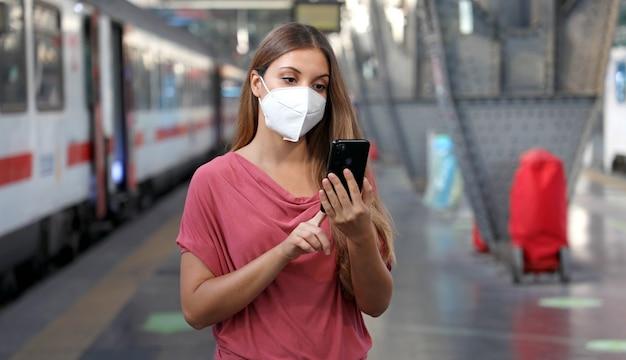 Casual vrouw met behulp van slimme telefoon in treinstation