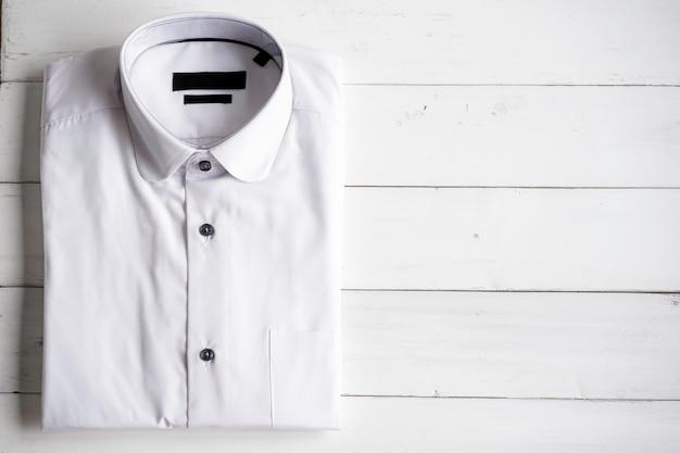 Casual wit formeel shirt vouwen in de plastic verpakking op wit hout