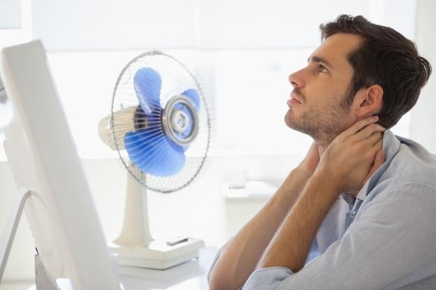 Casual zakenman zittend aan een bureau met elektrische ventilator