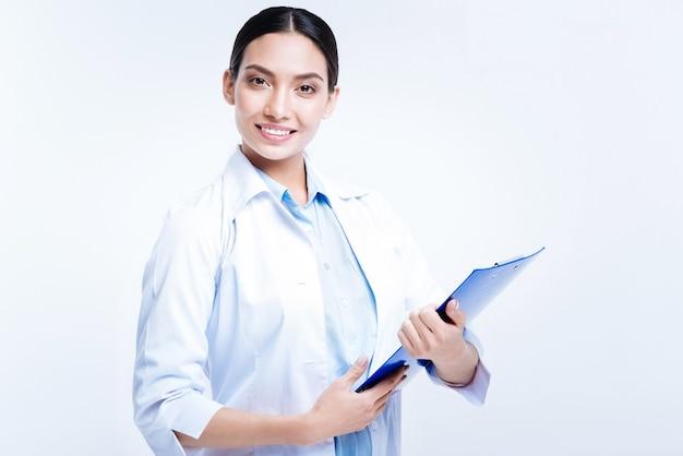 Casuïstiek bijhouden. mooie donkerharige jonge vrouw met een blauwe lakenhouder met de casussen van haar patiënten en poseren tegen een witte muur
