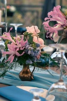 Catering evenement setting bloemen kaarsen blauwe servetten houten tafels evenement decoratie buitenshuis