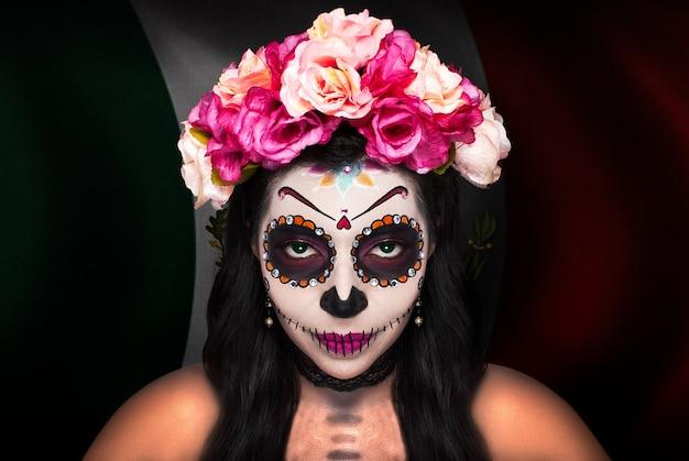 Catrina make-up dame met de vlag van mexico op de achtergrond
