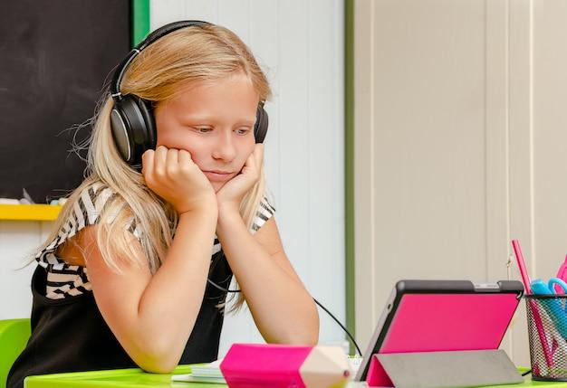 Causacian schattig schoolmeisje met oortelefoons is bezig met saai online thuisonderwijs. afstandsonderwijs concept. kopieer ruimte