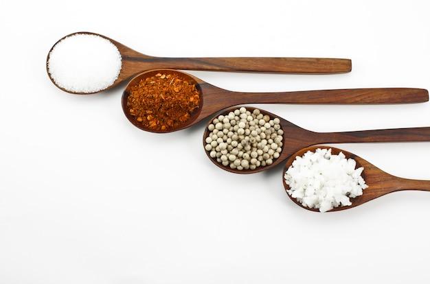 Cayennepeper, zout, suiker, peperkorrel op een houten lepel