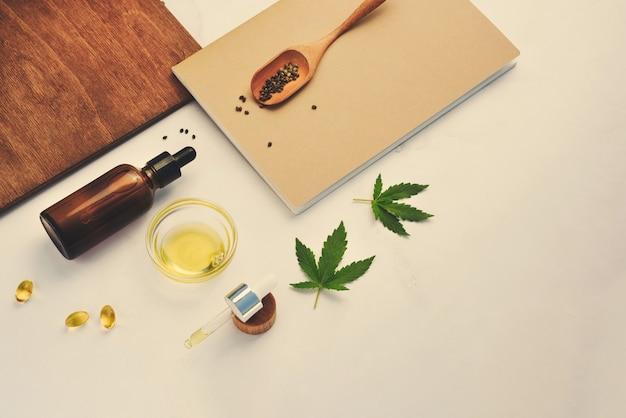 Cbd-olie, tinctuur met marihuanabladeren op een beige achtergrond. cannabis zaden