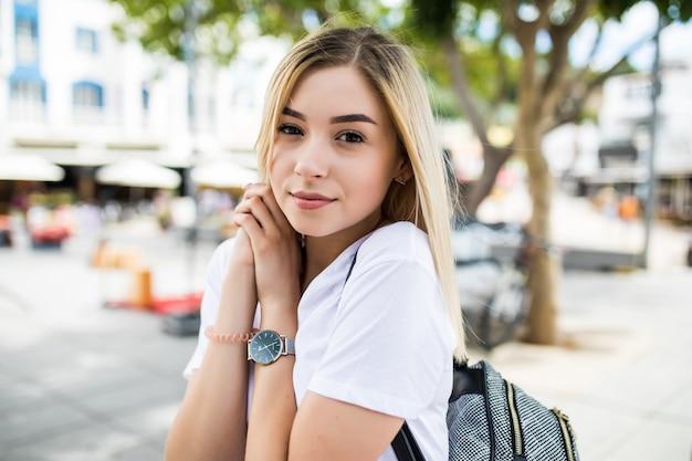 Cclose-up portret van mooie jonge vrouw kijken camera aanraken van de kin met de hand buitenshuis