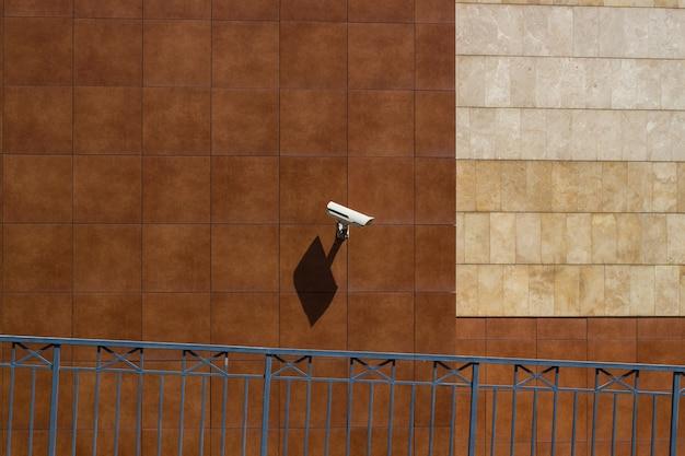 Cctv-camera geïnstalleerd in een winkelcentrummuur voor het bewaken van de veiligheid op een parkeerplaats