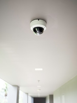 Cctv-camera op wit plafond bij loopbrug