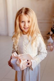 Ccute kleine blonde meisje in jurk in de buurt van de kerstboom