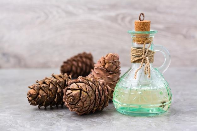 Cederolie in een fles en ceder kegels op tafel. behandeling van harsceder. alternatief medicijn